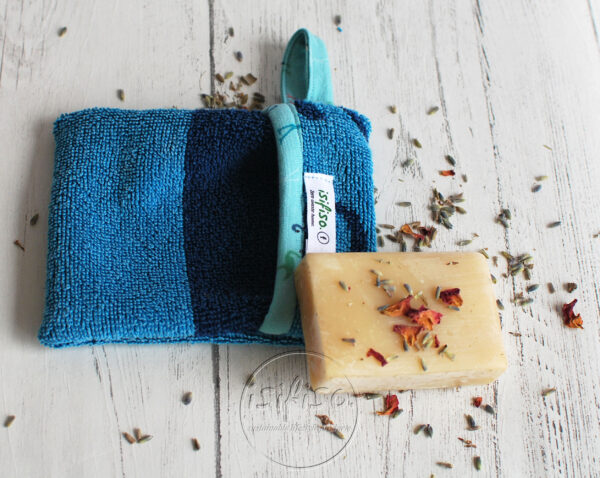 Turquoise soap mitt with contrast trim flat lay