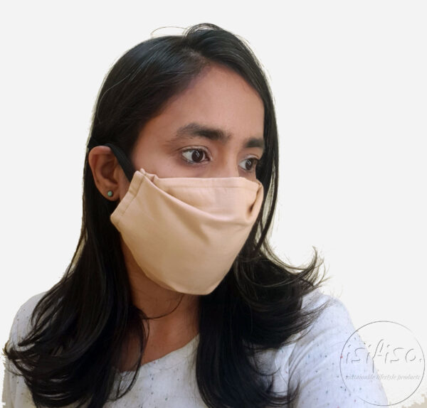 Beige coloured masks triple layer mask with nose wire and elasticated on a model