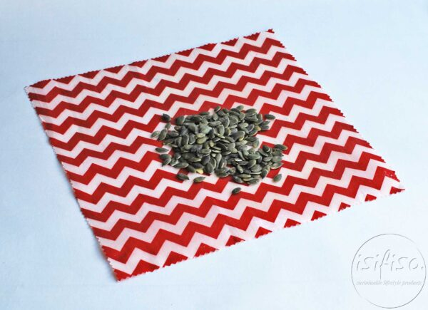 Red chevrons printed Beeswax wrap displayed with sunflower seeds (snacks)