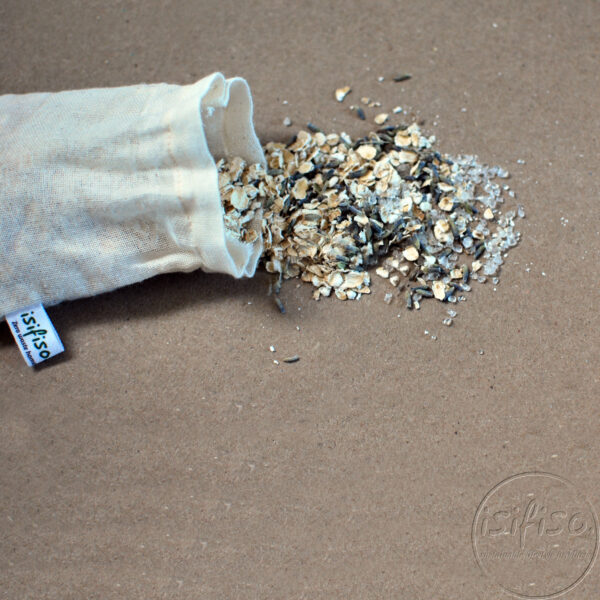 Bath tea bag with oats, salts and lavender spilled on brown background