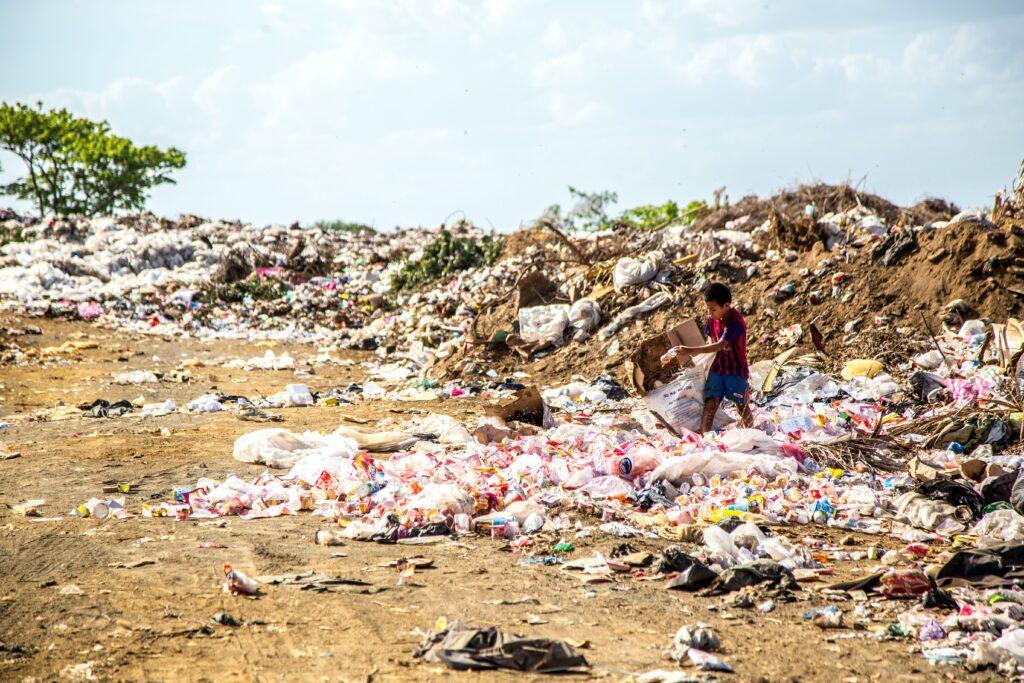 landfill waste with boy picking through rubbish