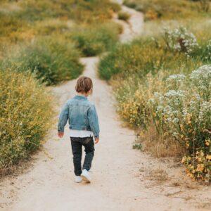 benefits of walking - child walking along a sandy path